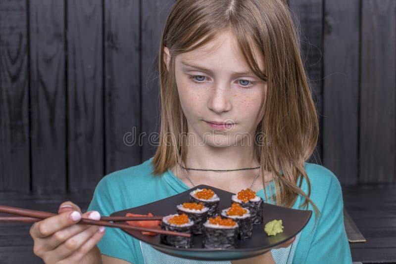 相当有寿司卷特写镜头画象的青少年的女孩,吃日本寿司的十几岁的女孩 库存照片