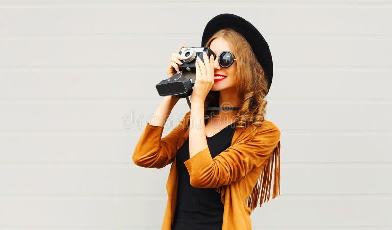 相当有戴一个典雅的帽子,棕色夹克的减速火箭的影片照相机的典雅的凉快的女孩 免版税库存照片