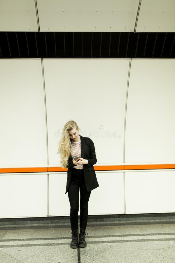 相当有手机的少妇在地铁 免版税库存照片