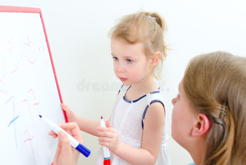 相当有教师的小女孩 免版税图库摄影
