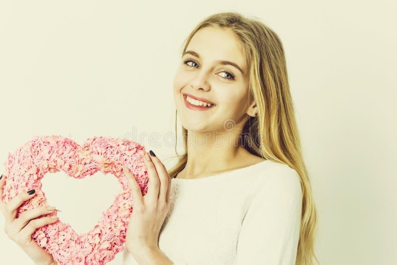 相当有桃红色柳条心脏的愉快的女孩为情人节 免版税库存图片