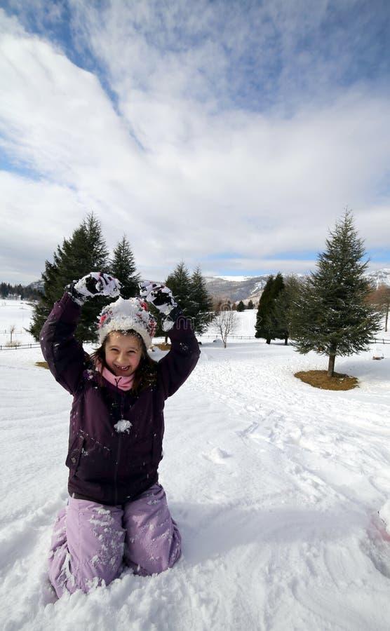 相当有演奏在雪我的羊毛贝雷帽的小女孩 免版税库存图片