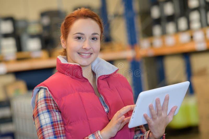 相当有片剂的年轻女性反对铲车在大仓库里 免版税图库摄影