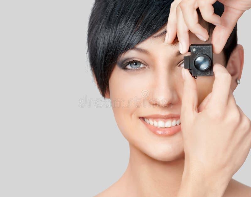 相当有玩具照片照相机的少妇的特写镜头面孔 图库摄影
