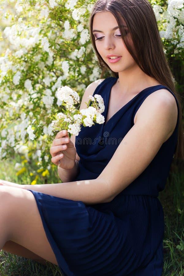 相当有白花的青少年的女孩在自然 免版税库存照片