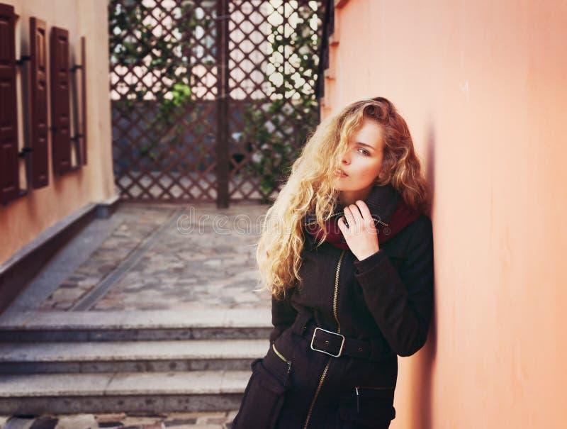 相当有看在照相机的长的卷发的年轻时尚妇女和摆在室外在墙壁附近在街道背景中 图库摄影