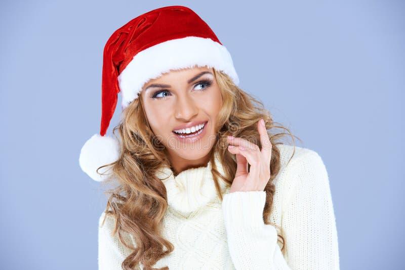 相当有红色圣诞老人帽子的愉快的妇女 免版税库存图片