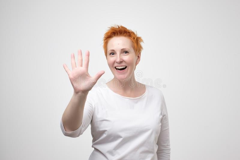 相当有红色头发的成熟妇女在显示5个或五个手指手势的白色T恤杉 免版税库存照片