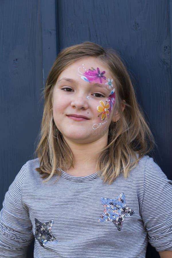 相当有花卉面孔绘画的小女孩 免版税库存照片