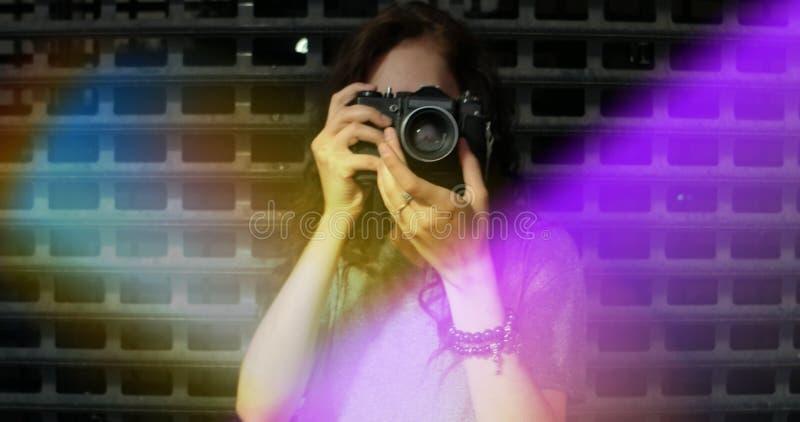 相当有葡萄酒照相机的少妇画象拍照片您, copyspace,五颜六色的轻的泄漏 免版税库存图片