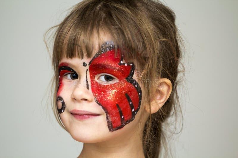 相当有蝴蝶绘画的小女孩画象在她的fa 免版税图库摄影