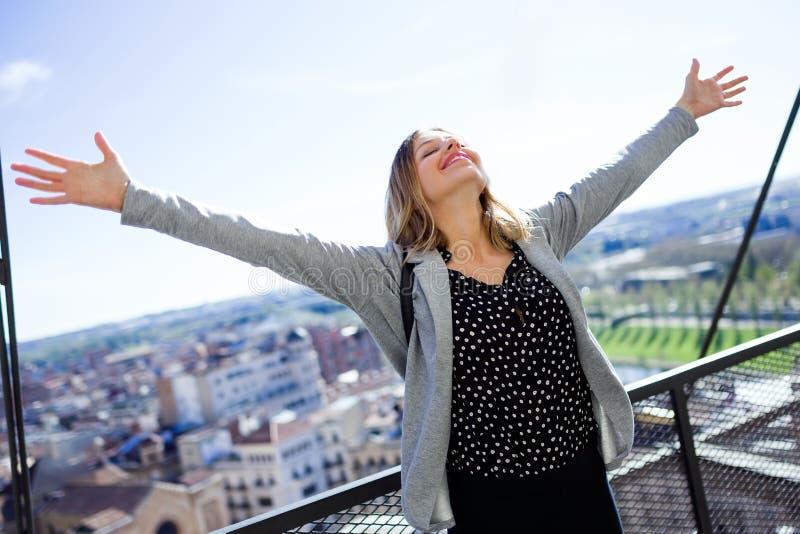 相当有被举的胳膊的少妇对天空享受时间的在高层建筑物现代屋顶  库存图片