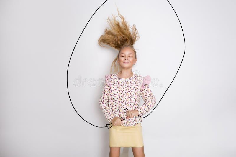 相当有长的金发跳绳和快乐微笑的小女孩 免版税库存图片