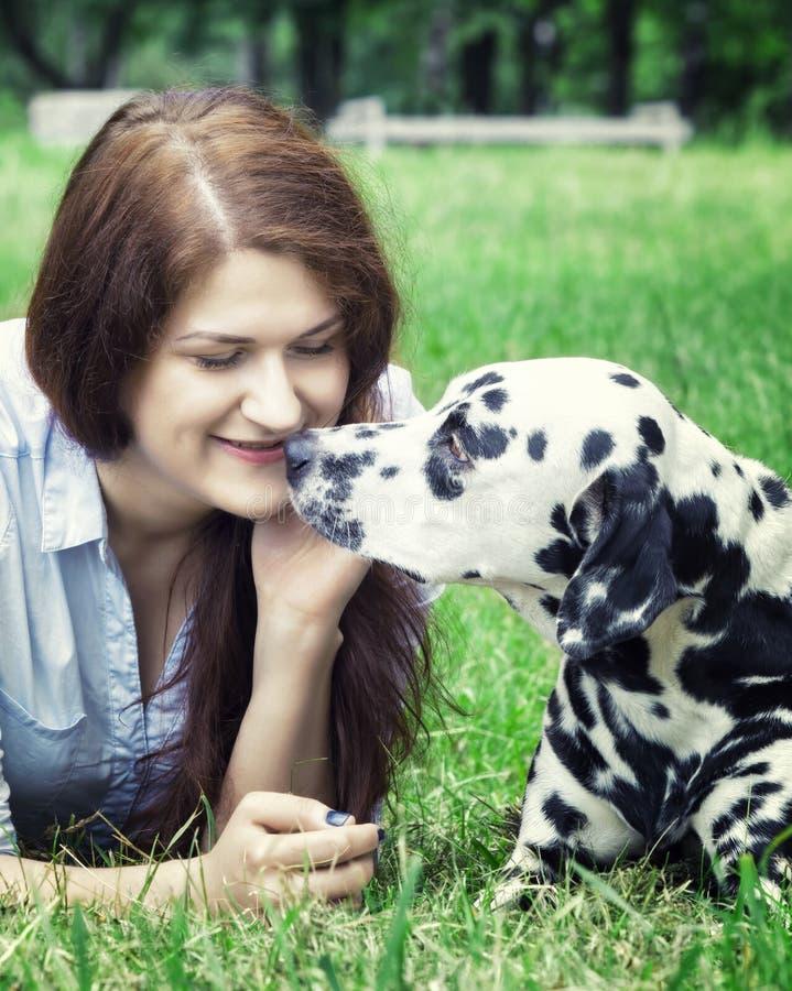 相当有长的黑发的美丽的妇女有达尔马希亚狗的 免版税库存照片