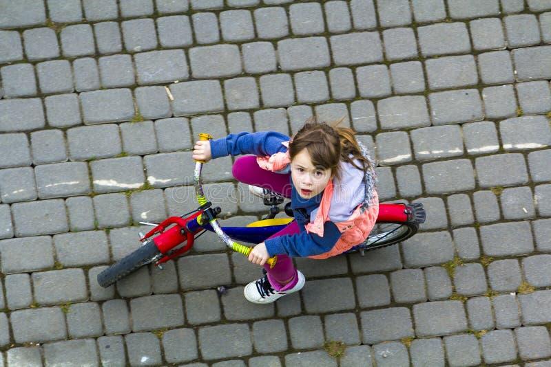 相当有骑自行车的长的浅褐色的头发的女孩顶视图在向上看凉快的春日 户外活动 H 免版税库存照片