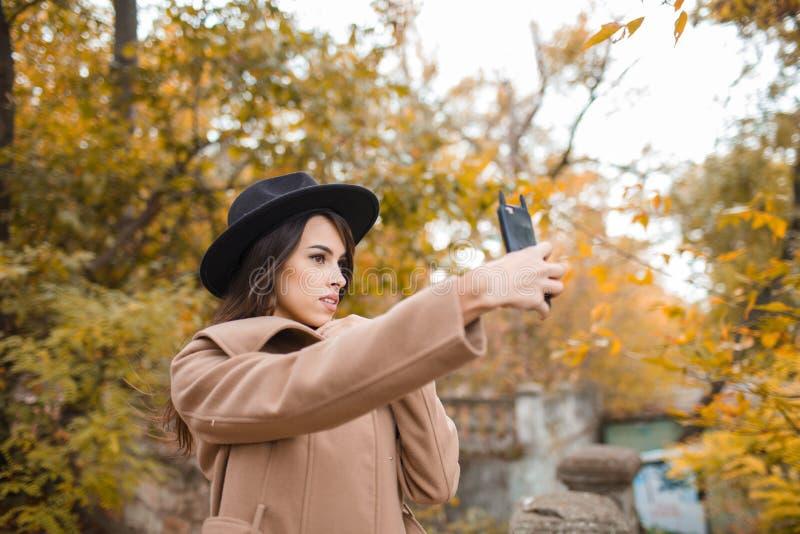 相当有黑帽会议的女孩走在公园的 免版税库存照片