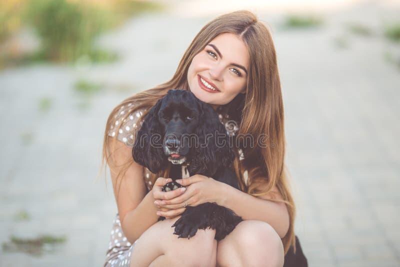 相当有黑猎犬狗的青少年女孩特写镜头画象  免版税库存图片