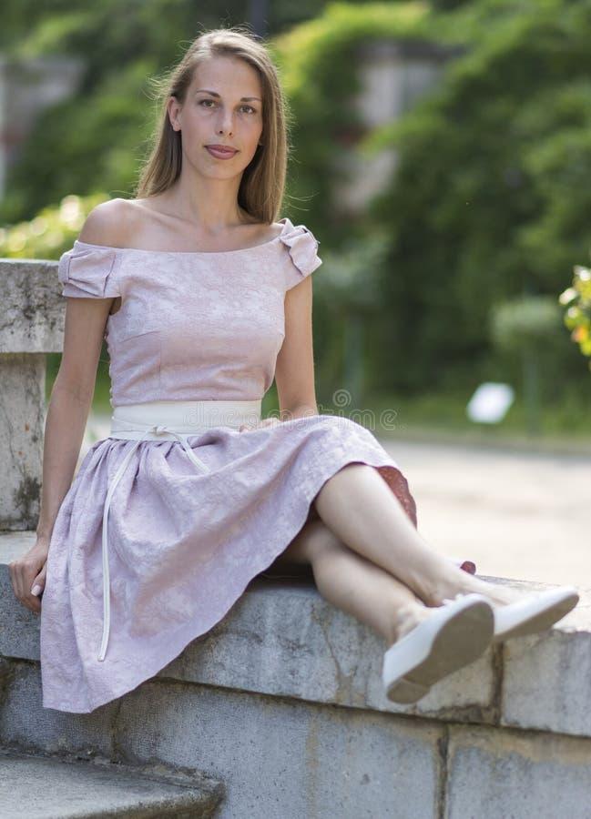 相当桃红色礼服的白女孩画象坐老石楼梯 免版税库存照片