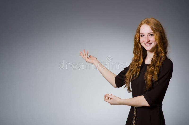 相当棕色礼服的红色头发女孩反对灰色 免版税库存图片