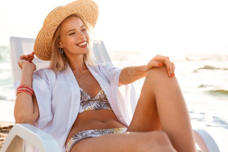 相当泳装和草帽smili的白肤金发的妇女20s照片  免版税库存图片