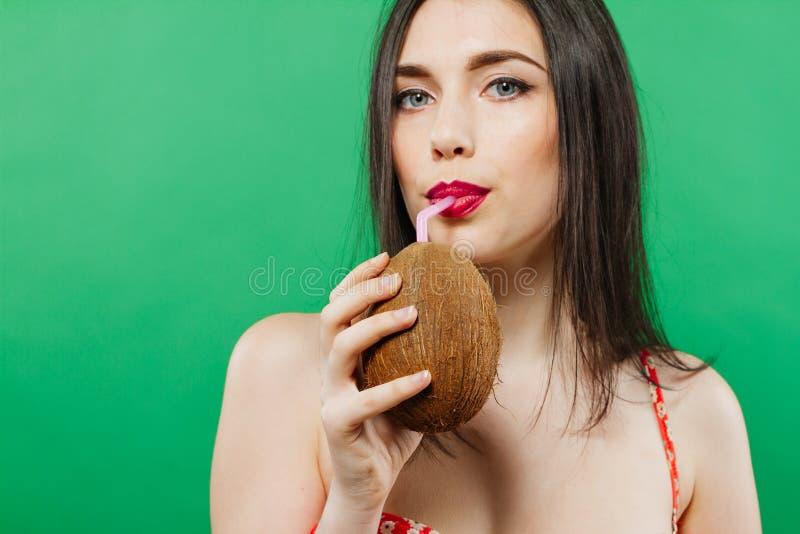 相当深色头发的在椰子的女孩饮用的鸡尾酒和看在绿色背景的照相机特写镜头画象  免版税库存图片