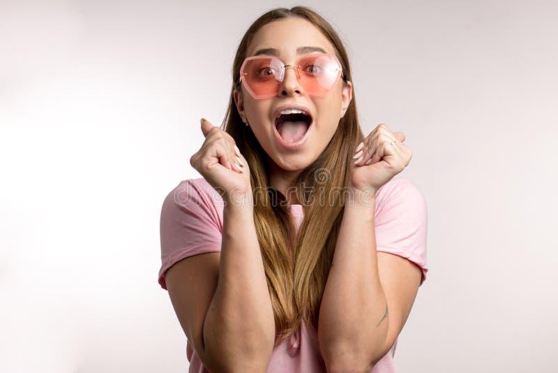 相当激动的愉快的女孩穿戴了偶然庆祝她的胜利 免版税库存图片