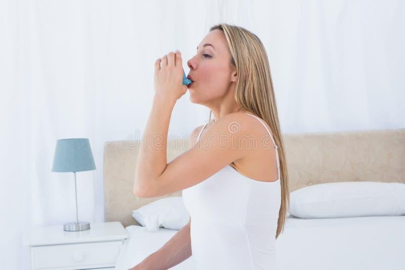 相当白肤金发使用哮喘吸入器 免版税库存照片