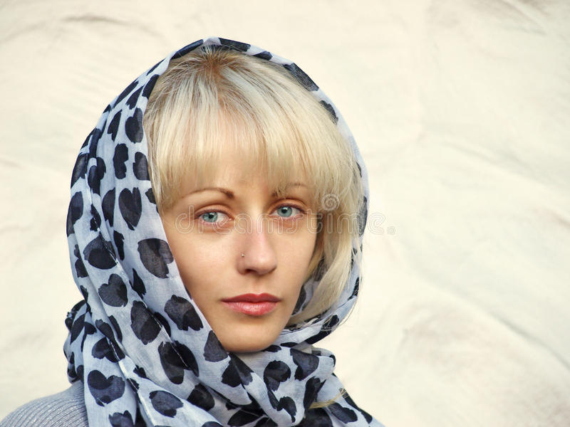 相当白肤金发在一条多斑点的围巾。 库存图片