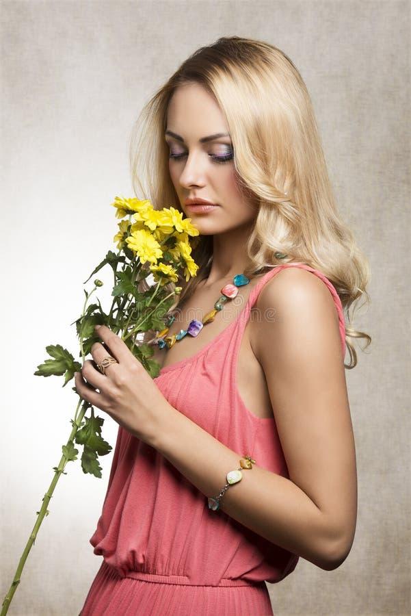 相当白肤金发的女孩嗅到的花 库存照片