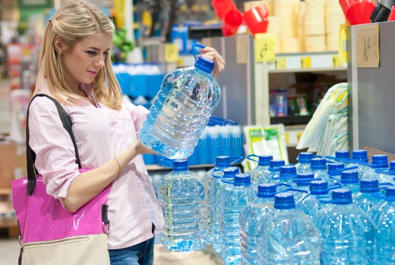 美丽的年轻白肤金发的妇女在选择清水的商店 库存图片