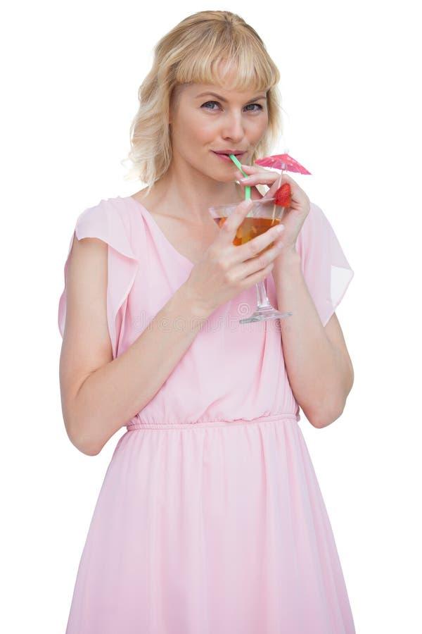相当白肤金发的妇女饮用的鸡尾酒 免版税库存图片