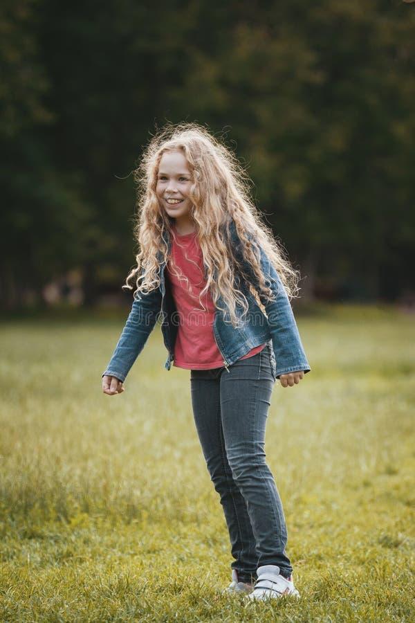 相当白肤金发的微笑的儿童佩带的牛仔裤夹克在公园 库存图片
