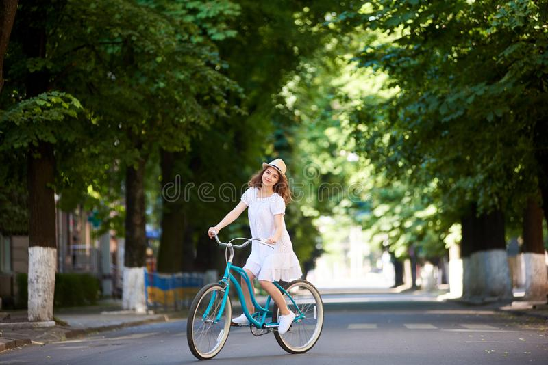 相当白色乘坐一条空的绿色街道的蓝色自行车中部的礼服和草帽的年轻女性 免版税库存图片