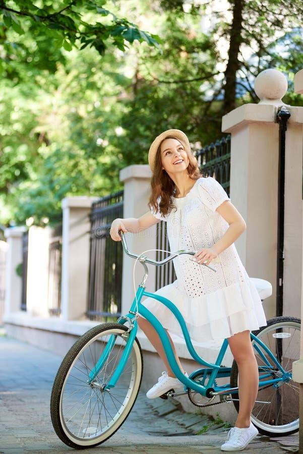 相当白色礼服和草帽adimiring的树的年轻女性,当骑蓝色葡萄酒自行车时 库存照片