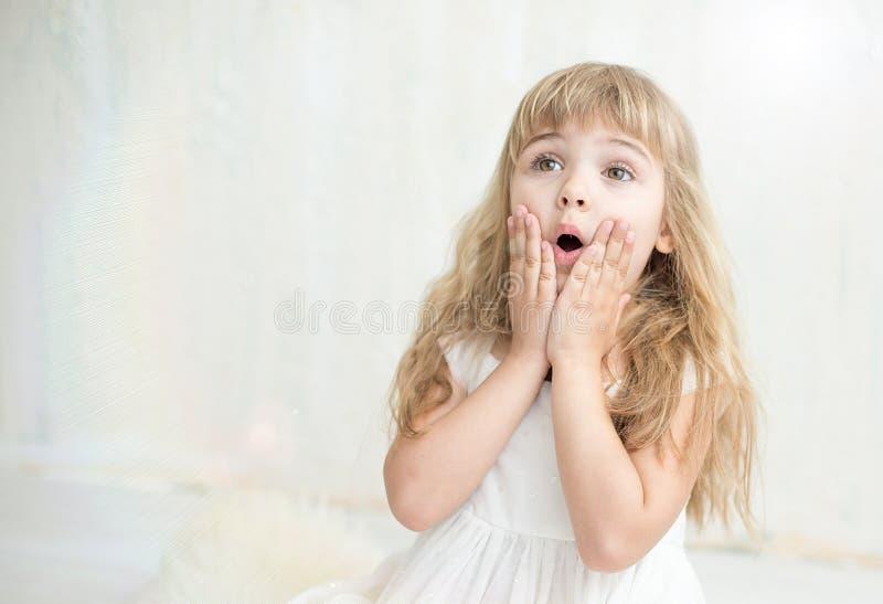 相当白色礼服的小女孩画象,她在面颊上惊奇并且把她的手放 免版税库存图片