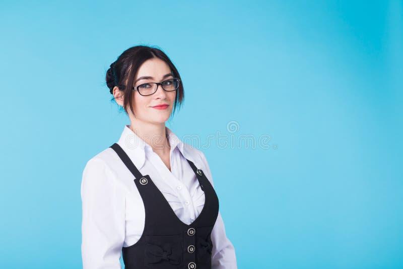 相当看在蓝色背景的玻璃和背心的年轻微笑的深色的妇女照相机 图库摄影