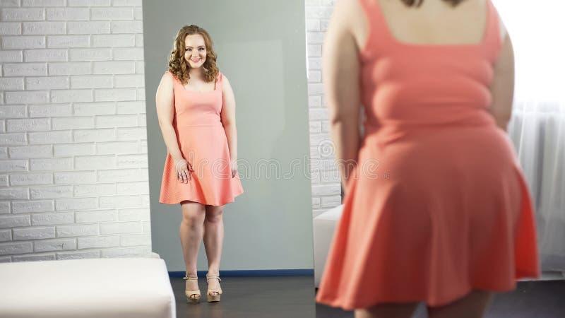 相当看在镜子的肥满夫人,满意与出现,身体阳 免版税库存照片