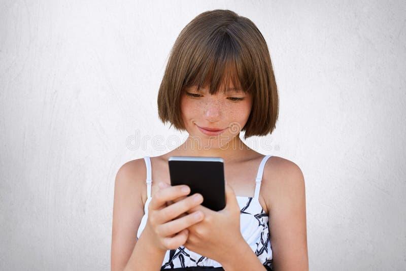 相当看殷勤地入她巧妙的电话的小女孩,当在网上观看动画片使用自由互联网连接时 孩子p 免版税库存照片