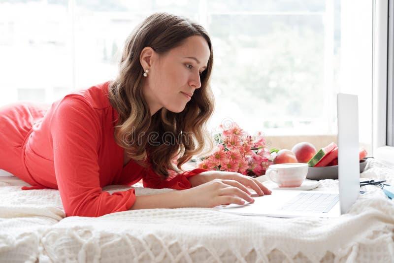 相当研究在床a上的膝上型计算机的一件红色长袍的白肤金发的妇女 库存照片