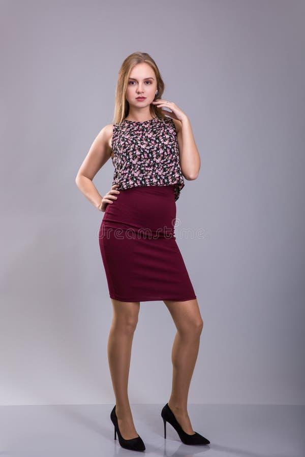 相当穿红色裙子和花卉图案女衬衫的女孩 正大小 免版税图库摄影