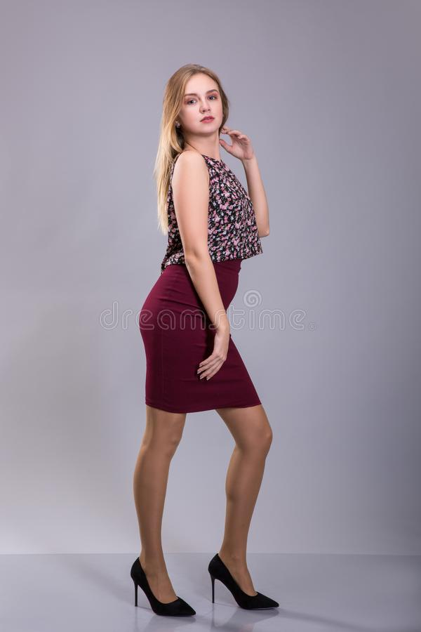 相当穿红色裙子和花卉图案女衬衫的女孩 正大小 库存图片