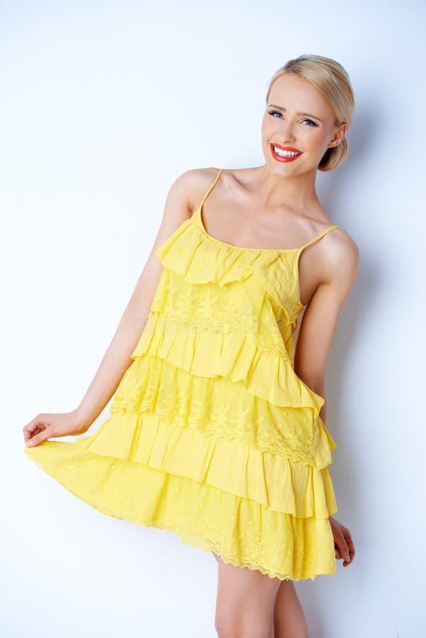 相当穿黄色礼服的端庄的妇女 免版税库存图片