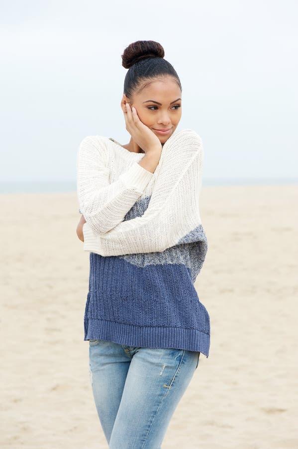 相当站立在单独海滩的少妇在毛线衣和牛仔裤 免版税库存图片