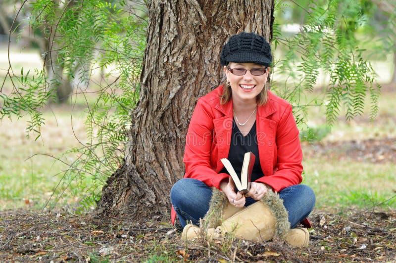 相当笑户外在结构树下的愉快的少妇 免版税库存照片