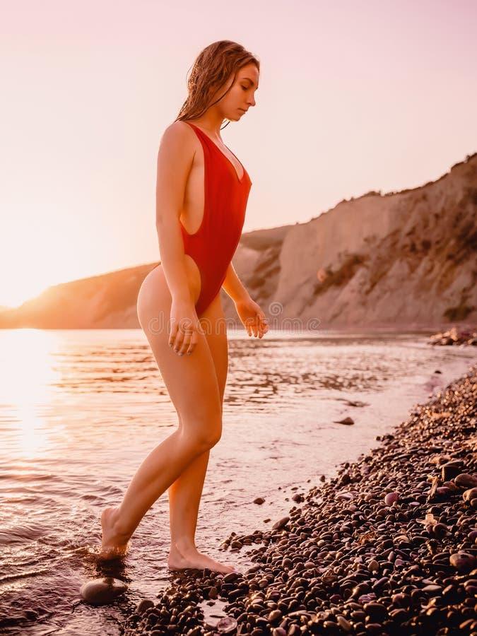 相当红色游泳衣的亭亭玉立的妇女在有温暖的日落颜色的海洋 图库摄影