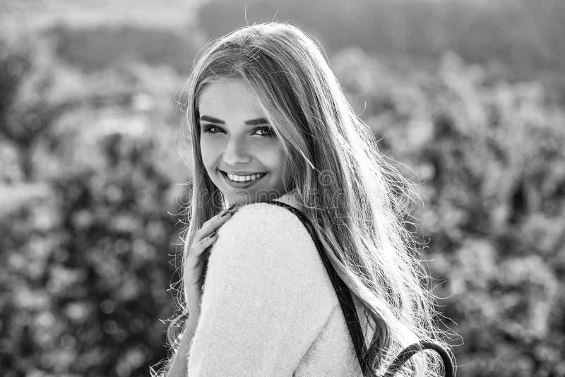 相当美丽的与蓝眼睛和长的卷曲金发的妇女性感的模型在外套在晴天微笑户外  免版税图库摄影