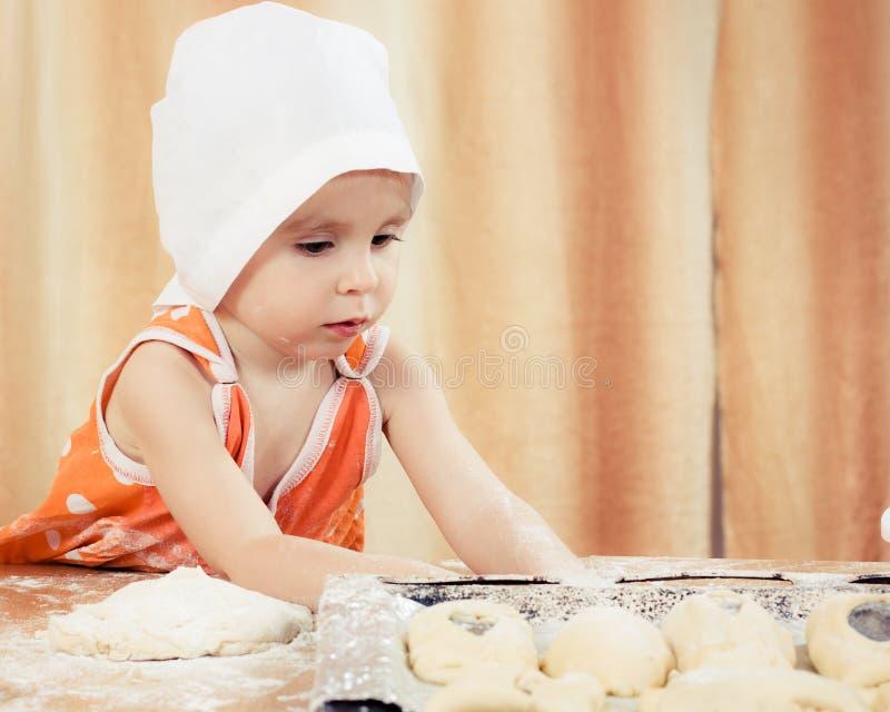 相当美丽的女孩在做饼的桌上。 免版税库存图片