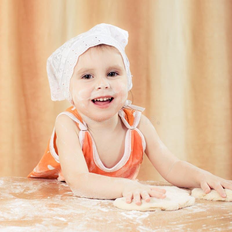 相当美丽的女孩在做饼的桌上。 免版税库存照片