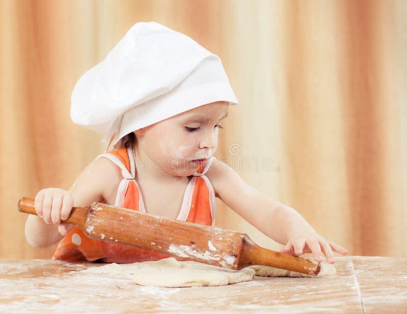 相当美丽的女孩在做饼的桌上。 库存照片