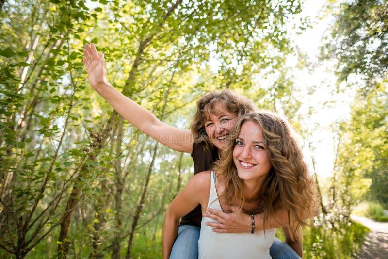 相当背上给乘驾的青少年的女儿她无忧无虑的母亲 免版税图库摄影